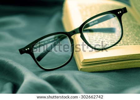 selective focus of  the reading Eyeglasses with opened book on dark green silky fabric - stock photo