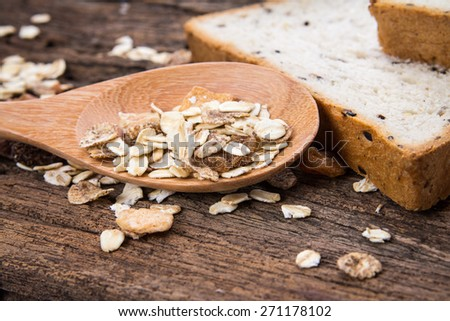 selective focus of whole grain cereal flakes which mixed warming cinnamon , red skin apple , golden raisins and roasted hazelnuts on wooden plate - stock photo