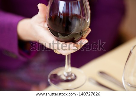 Selective focus of woman's hand holding wine glass at restaurant table - stock photo