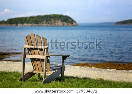 Selective focus on a lone deck chair overlooking the water on a sunny day. Bar Harbor, Maine, USA