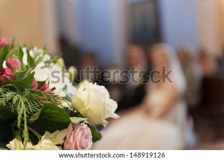 Selective focus on a wedding bouquet in church with bride and groom in the bokeh area
