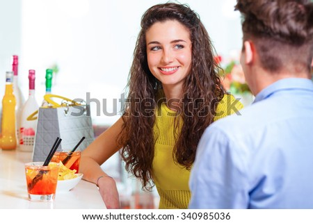 Selective focus on a young smiling girl talking to the boy in front of her, with cocktail at the bar counter  - stock photo