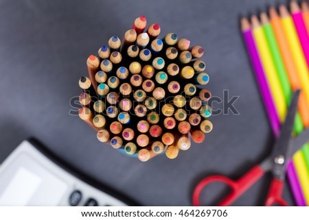 Selective focus on close up top view of colorful pencil tips with school supplies and erased chalkboard in background. Back to school concept.