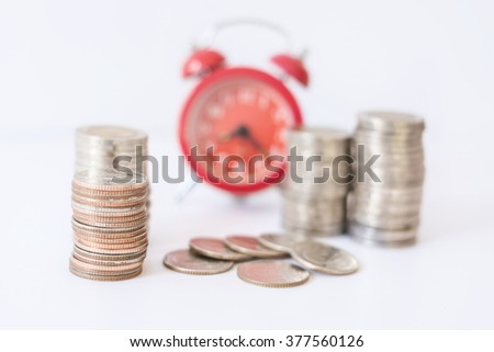 selective focus on coins front of blur red alarm clock, concept on time to work at make money. - stock photo