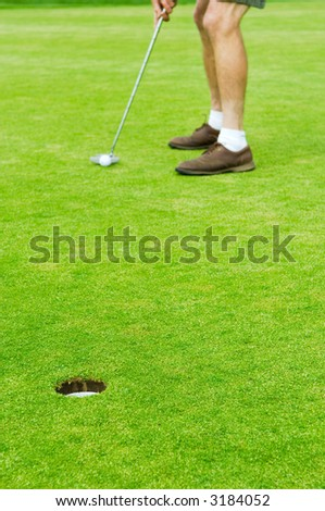 Selective focus on cup with defocused man standing in background addressing the ball, about to putt. - stock photo
