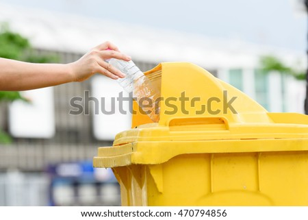 Selective focus on hand dropping empty plastic bottle to the yellow garbage bin.
