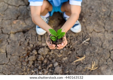 Selective focus on hand of young Thai boy carry little seedling on dry and crack empty land. Earth day concept. - stock photo