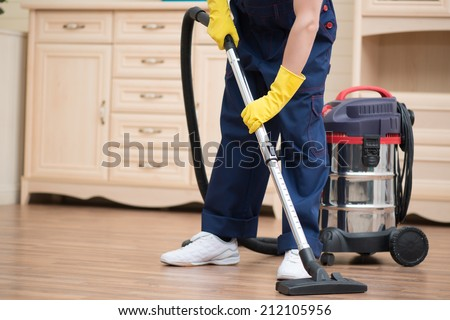 Selective focus on janitor wearing blue overalls vacuuming the floor in the office. Commode on background - stock photo