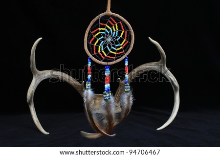 Selective focus on Native American Dreamcatcher, symbolic object of sacred and spiritual beliefs, with deer antlers against black background. - stock photo