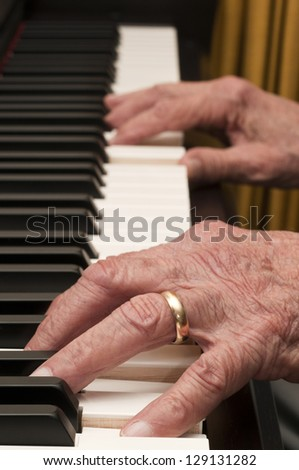 Selective focus on old hands playing the piano - stock photo