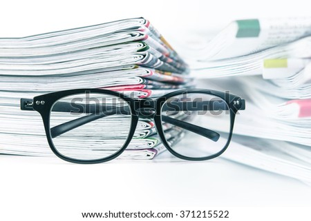 selective focus on reading eyeglasses with stacking of the newspaper background ,business information concept
