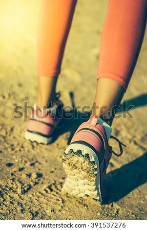 Selective focus on running shoes at the beach - vintage effect and sun flare filter processing