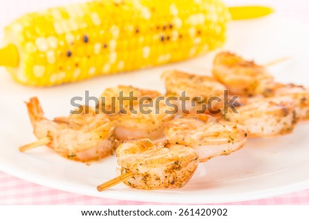 Selective focus on Shrimp seasoned in Old Bay mixture grilled on wooden skewers and served with roasted corn on the cob.  Shallow depth of field, closeup. - stock photo