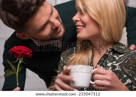 Selective focus on the beautiful surprised fair-haired young woman wearing blouse and jeans looking happy at her boyfriend giving her wonderful red rose - stock photo