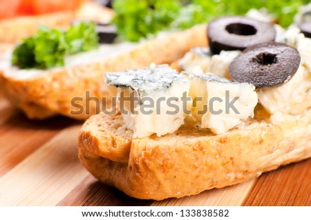 Selective focus on the blue cheese on bruschetta - stock photo