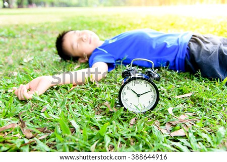 Selective focus on the classical black alarm clock model, in front of the sleeping young boy on green lawn in the park in day time. - stock photo
