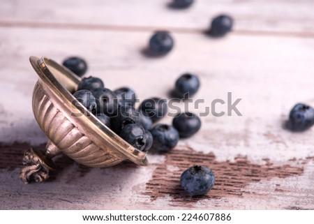 Selective focus on the copper top with little blackberries in it lying on the wooden table - stock photo