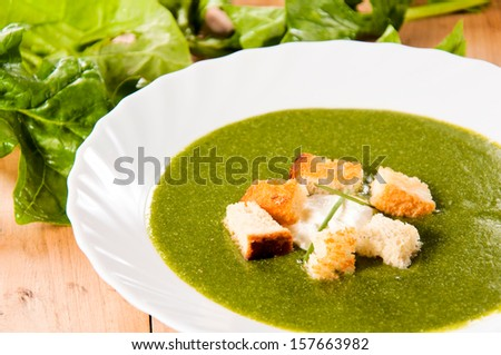 Selective focus on the dried crust in cream spinach soup - stock photo