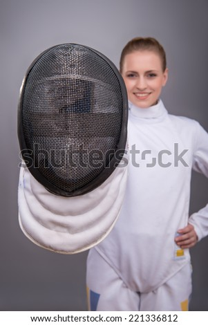 Selective focus on the fencing mask in the hands of smiling fair-haired girl wearing fencing costume on background - stock photo
