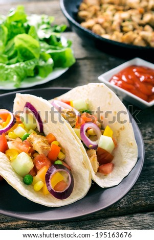 Selective focus on the front tortilla sandwich stuffed with chicken meat and vegetables  - stock photo