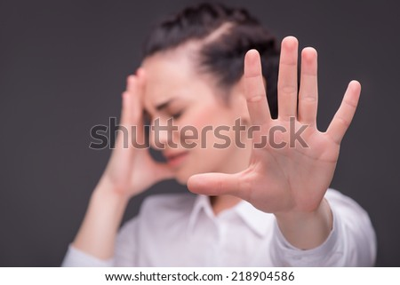 Selective focus on the hand of dark-haired upset beautiful woman wearing white blouse standing on background