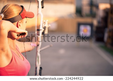 Selective focus on the lovely young fair-haired woman wearing pink T-shirt and black skirt pulling the bowstring. The target on background - stock photo