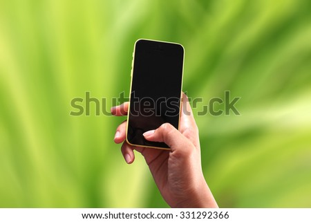 selective focus on the phone with beautiful blur green field  - stock photo