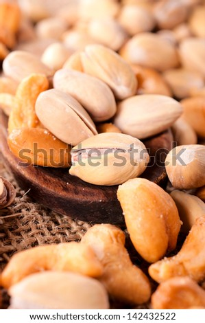 Selective focus on the pistachio on wooden spoon - stock photo