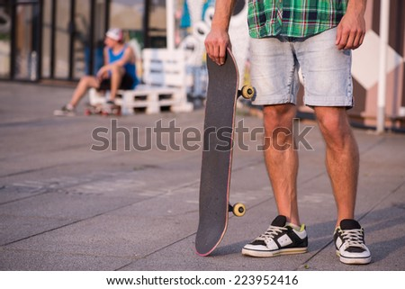 Selective focus on the young man wearing shorts checked T-shirt and trainers standing with his skateboard on the street