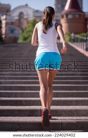 Selective focus on the young sexy woman wearing white T-shirt and blue shorts standing back in the red jogging shoes on the stairs on background - stock photo
