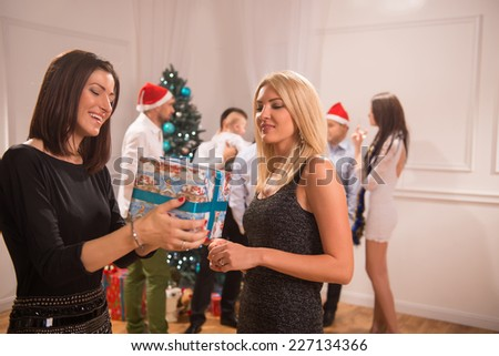 Selective focus on two happy smiling friends standing together sharing presents with each other. Their friends celebrating New Year on background - stock photo