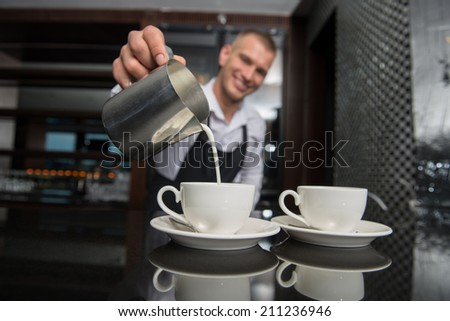 Selective focus on two white cups of coffee and metal jar with milk. Handsome young smiling barista wearing white shirt and black apron pouring the milk on background - stock photo