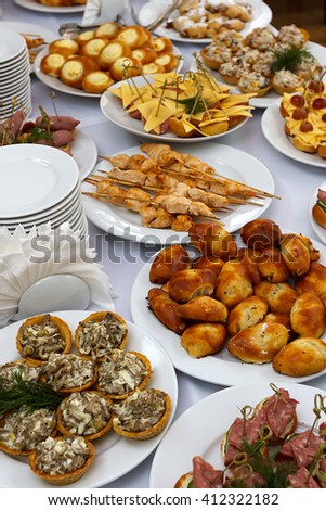 Selective focus photo, catering banquet table with baked food snacks, sandwiches, cakes, cups and plates, self serve, open buffet dinner, close up - stock photo