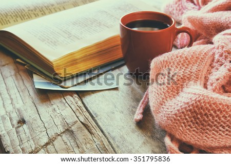 selective focus photo of pink cozy knitted scarf with to cup of coffee and open book on a wooden table. style retro filtered  - stock photo