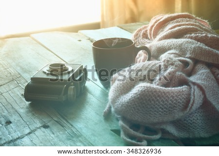 selective focus photo of pink cozy knitted scarf with to cup of coffee next to old photo camera on a wooden table. faded style retro filtered and toned  - stock photo
