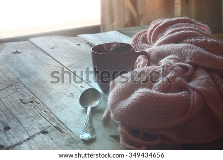 selective focus photo of pink cozy knitted scarf with to cup of coffee on a wooden table. faded style retro filtered - stock photo