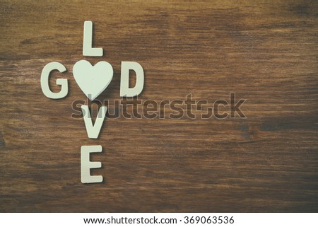 selective focus photo of The words love is god made with block wooden letters on wooden background. religion concept - stock photo