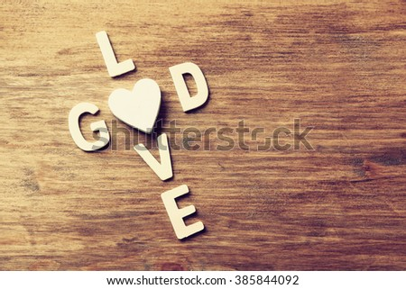 selective focus photo of The words love is god made with block wooden letters on wooden background. religion concept. vintage filtered and toned  - stock photo