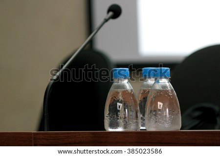 Selective focus photo of three bottles of water on table with blank screen, microphone and chairs on background in conference room, horizontal view - stock photo