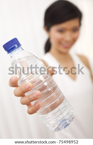 Selective focus photograph of beautiful Chinese Asian Oriental girl or woman holding bottle of fresh pure mineral water to camera