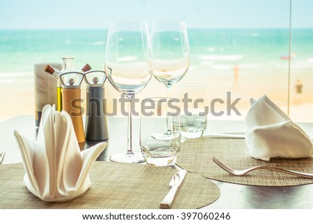 Selective focus point at Table setting for dinner with wine glass and etc in restaurant - Vintage Light filter - stock photo