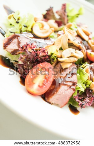 Selective focus point on Smoked duck salad with vegetable and sweet sauce in white plate - Healthy food style