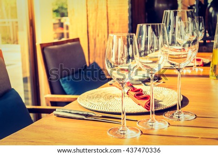 Selective focus point on wine glass with table setting for dinner in restaurant interior - Vintage Filter and Sunflare effect