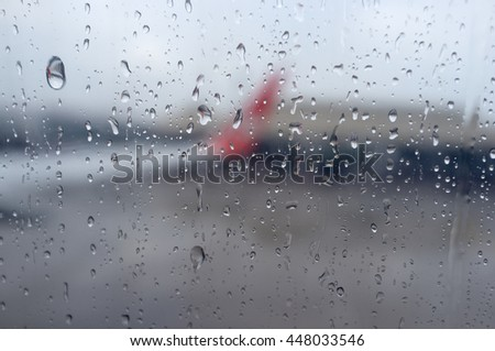 selective focus rain drop form window seat inside airplane  with blurred wing background
