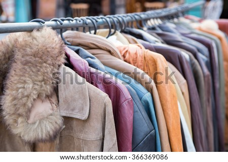 Selective focus second hand of Winter clothes hanged on a clothes rack - stock photo