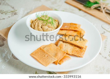 Selective focus Set of Traditional Eastern appetizer hummus with chips on the white plate  on served in eco style restaurant table - stock photo