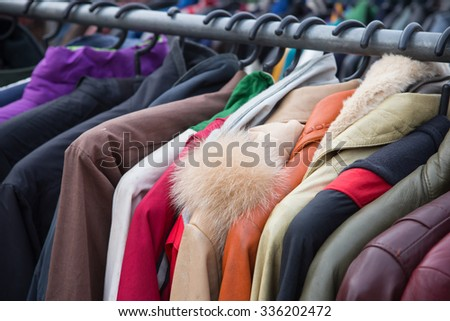 Selective focus some used leather clothes hanging on a rack in market - stock photo