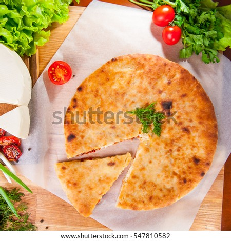 Selective Focus vegetable closed pies with cheese and sun-dried tomatoes on the table. Composition of ingridients. Top view