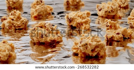 Selective focus with shallow depth of field on home made chocolate chip cookies on tin foil just before they go into the oven. Dough is freshly made and gooey. Several cookies scattered about - stock photo