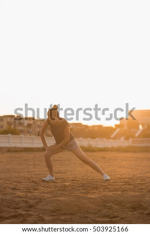 Selective focus Young girl in a gray T-shirt and shorts is engaged in yoga on the beach one morning at dawn the sun. Meditation in nature. The concept of sports, fitness, healthy lifestyle